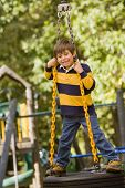 Hispanic boy standing on tire swing