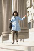 Hispanic businesswoman walking down steps