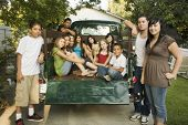 Hispanic teenagers and young adults in back of truck
