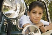 Hispanic boy leaning out of car window