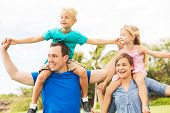 Portrait of Happy Family of Four Outside Playing