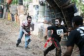 MUSKOGEE, OK - Sept. 13: Athletes run through zombie-infested forest during the Castle Zombie Run at the Castle of Muskogee in Muskogee, OK on September 13, 2014.