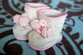 picture of pom poms  - small white crocheted booties with pink trim and pom-poms
