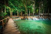 stock photo of wild adventure  - Jungle landscape of tropical rain forest landscape with wooden bridge and amazing turquoise water of Kuang Si cascade waterfall - JPG