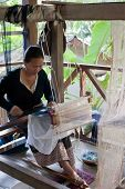 Woman Weaving Silk In Traditional Way At Manual Loom. Laos
