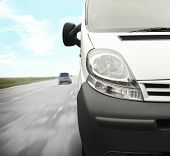 The front part of white minivan on the road background