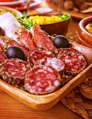 Tasty cold cuts on wooden table at home, slices of salami, pieces of pepperoni and ham, festive menu, different kind of smoked meat