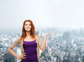 business, advertising and people concept - smiling teenage girl in casual clothes holding something on her palm over city background