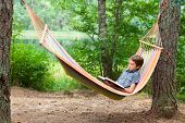 Boy lying in hammock reading a book outdoors