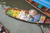 The woman sale fruits on boat at Damnoen Saduak Floating Market