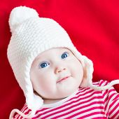 image of blanket snow  - Happy Laughing Baby Girl With Beautiful Blue Eyes Wearing A White Knitted Hat Relaxing On A Red Blanket - JPG