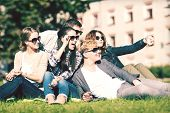 summer holidays and teenage concept - group of teenagers taking photo outside with smartphone