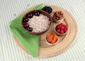 Big round wooden plate with raisins, raspberries, oatmeal, nuts and dried apricots on fabric background