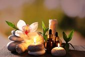 Spa composition with herbal massage bags, candle and bamboo on table on natural background