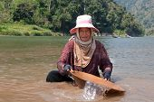 picture of ou  - woman washing gold in river portrait of asian at nam ou in Laos - JPG