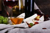 Supper consisting of Camembert and Brie cheese, honey, wine and grapes on napkin on curtain background