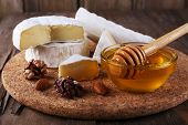 Camembert cheese, nuts, honey and bread on cutting board on wooden background