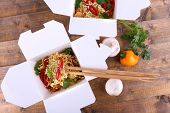 picture of chinese parsley  - Chinese noodles in takeaway boxes with mushrooms and parsley on wooden background - JPG