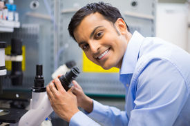 image of histology  - Closeup portrait young friendly scientist looking into microscope - JPG