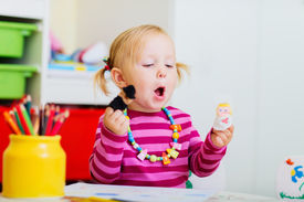 foto of daycare  - Adorable toddler girl playing with finger puppets at home or daycare - JPG