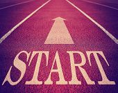 Concept of start with an arrow on a track for business toned with a retro vintage instagram filter effect app or action with a grunge look