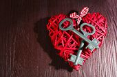 Keys on wicker decorative heart on wooden background