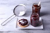 Delicious cookie with jam and powdered sugar on plate on wooden background