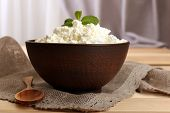 Cottage cheese in bowl with spoon on table close up
