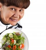 Pension age good looking woman eating  salad