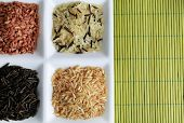 Different types of rice on plate on bamboo background