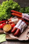 Assortment of thin sausages, mustard in bowl and spices on cutting board, on wooden background