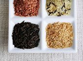 Different types of rice on plate on fabric background
