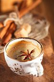A cup of spiced coffee with anis star and cinamon sticks and sugar