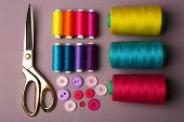 Multicolor sewing threads with buttons and scissors on wooden background
