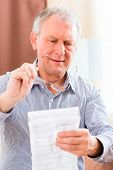 Old man reading  medicament package insert at home with glasses