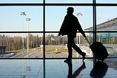 Silhouette Of Man With Luggage Walking Left Near Window In Airport Focus On Street