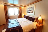 stock photo of cruise ship  - ship cabin with big double bed and window summer day - JPG