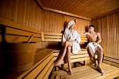 picture of sauna  - Young couple sitting on a wooden bench at the sauna - JPG