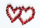 pic of two hearts  - Ripe pomegranate seeds in form of two hearts on white background - JPG