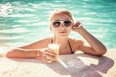 Little Blond Girl With Glass Of Cocktail In Swimming Pool