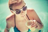 Little Blond Girl Drinks Cocktail In A Swimming Pool