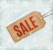 Sale paper tag on background with snowflakes and snow.