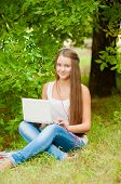 Teen girl works with the laptop on the grass