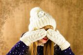 stock photo of knitted cap  - young girl in a knitted white cap and mittens on brown background - JPG