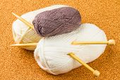 Roll Of White And Brown Soft Knitting Yarn And Wooden Needles