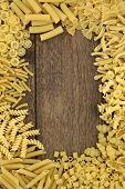 Pasta food abstract background border over old oak wood.