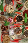 Spice and herb selection in wooden bowls and loose over old grunge paper background.