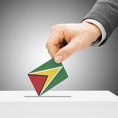 Voting Concept - Male Inserting Flag Into Ballot Box - Guyana