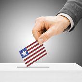 Voting Concept - Male Inserting Flag Into Ballot Box - Liberia