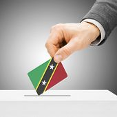 Voting Concept - Male Inserting Flag Into Ballot Box - Saint Kitts And Nevis